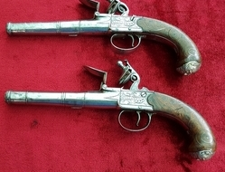 A fine pair of silver mounted English Queen Anne style flintlock ...